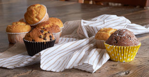 Several different muffins on a wooden table. Stock Photography