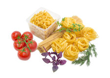 Several different uncooked pasta, tomatoes, sprigs of basil, dil Royalty Free Stock Image