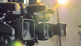 Several different video cameras focused in bright warm light.