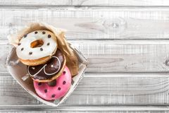 Several donuts are in the box, on an old wooden table, top view royalty free stock photography