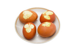 Several Easter eggs with leaf patterns on a saucer Stock Photos