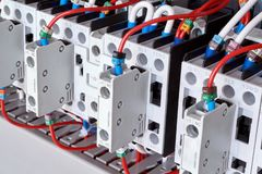 Several electric magnetic starters or contactors with additional contacts. Contactors are arranged in a row with wires connected to them. Connection of wires stock image