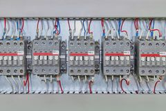 Several electrical contactor on a mounting panel in electrical closet. Stock Photo