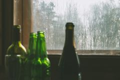 Several empty bottles of alcohol near the dirty window. Selective focus. Alcoholism, drunkenness, loneliness and depression royalty free stock photos
