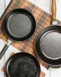 Several empty cast-iron frying pans on a white wooden background. View from above. royalty free stock image