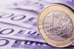 Several 500 euro banknotes and coins are adjacent. Symbolic photo for wealt.Euro coin balancing on stack with background of bankno Royalty Free Stock Images