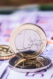 Several 500 euro banknotes and coins are adjacent. Symbolic photo for wealt.Euro coin balancing on stack with background of bankno Royalty Free Stock Photos