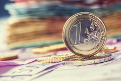Several 500 euro banknotes and coins are adjacent. Symbolic photo for wealt.Euro coin balancing on stack with background of bankno. Tes stock image