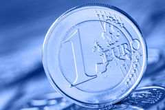 Several 500 euro banknotes and coins are adjacent. Symbolic photo for wealt.Euro coin balancing on stack with background of bankno Royalty Free Stock Photography