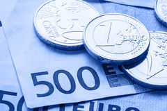 Several 500 euro banknotes and coins are adjacent. Symbolic photo for wealt.Euro coin balancing on stack with background of bankno. Tes stock images