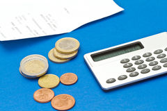 Several euro coins, bill and calculator. On blue background Stock Images