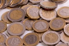 Several euro coins at different positions on a white background stock photos