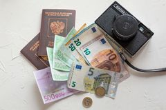 Euro banknotes,some coins and passports. Preps to the vocation o. Several euros on white concrete table, passports and coins stock images