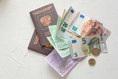 Euro banknotes,some coins and passports. Preps to the vocation o. Several euros on white concrete table, passports and coins stock image