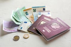 Euro banknotes,some coins and passports. Preps to the vocation o. Several euros on white concrete table, passports and coins royalty free stock photos