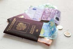Euro banknotes,some coins and passports. Preps to the vocation o. Several euros on white concrete table, passports and coins royalty free stock image