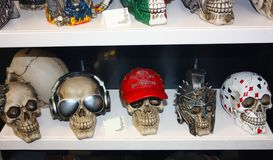 Several fake plastic skulls disguised with cute and funny accessories arranged on a shelf lined up for sale.  royalty free stock photos