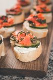 Lox and Cream Cheese with Capers, a Slice Cucumber and a Squeeze. Several finger sandwiches with smoked salmon and cream cheese cover a cutting board.  Capers Royalty Free Stock Photography