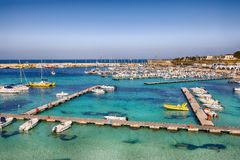 Several fishing boats at the Otranto harbour - coastal town in Puglia with turquoise sea. Italian vacation. Town Otranto, province of Lecce in the Salento stock photography