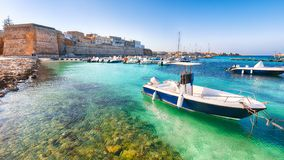 Several fishing boats at the Otranto harbour - coastal town in Puglia with turquoise sea. Italian vacation. Town Otranto, province of Lecce in the Salento stock images