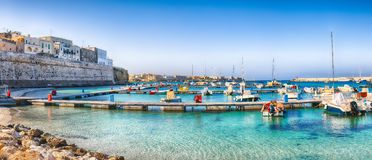Several fishing boats at the Otranto harbour - coastal town in Puglia with turquoise sea. Italian vacation. Town Otranto, province of Lecce in the Salento stock photo