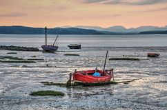 Fishing boats and mudflats at dusk. Several fishing boats on the transition between beach and mudflats in Morecambe Bay, Lancashire, England at dusk, with the Stock Photography