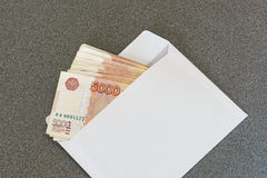 Several five thousandth ruble notes in a clean white envelope laying on a gray table Royalty Free Stock Photos