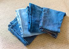 Stack of blue jeans.Shades of denim fabric. Several folded denim clothes are on the sofa. Shades of blue denim fabric royalty free stock images