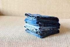 Stack of blue jeans.Shades of denim fabric. Several folded denim clothes are on the sofa. Shades of blue denim fabric stock image