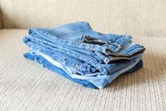 Stack of blue jeans.Shades of denim fabric. Several folded denim clothes are on the sofa. Shades of blue denim fabric royalty free stock photo