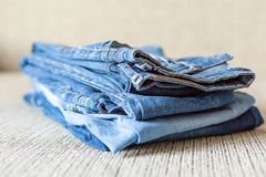 Stack of blue jeans.Shades of denim fabric. Several folded denim clothes are on the sofa. Shades of blue denim fabric stock images