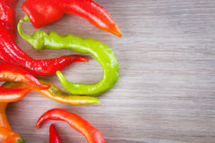 Several fresh red hot chili peppers on a wooden background Royalty Free Stock Image