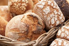 Several fresh tasty loaves of white and black bread. Delicious fresh loaves of rye and wheat bread to lie in a basket in a shop window or in a bakery royalty free stock photography