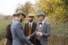 Several gangsters are discussing something on the street. Retro. Outdoors. Several gangsters in suits and hats are discussing something on the street among the Stock Photos
