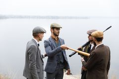Several gangsters, with weapons and beats argue about something. Retro. Outdoors. Several dangerous gangsters in suits and hats, with weapons and beats argue Royalty Free Stock Photos