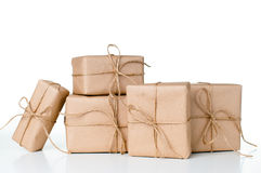 Several gift boxes, postal parcels. Wrapped in brown kraft paper tied with a rope on a white background, isolated royalty free stock image
