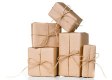 Several gift boxes, postal parcels. Wrapped in brown kraft paper tied with a rope on a white background, isolated stock photography