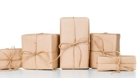 Several gift boxes, postal parcels. Wrapped in brown kraft paper tied with a rope on a white background, isolated royalty free stock photography