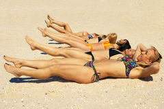 Several girls in bikini lying on sandy beach Stock Photos