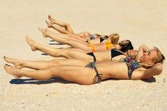 Several girls in bikini lying on sandy beach Stock Photos