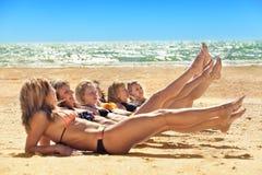 Several girls in bikini lying on sandy beach Royalty Free Stock Photos