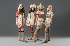 Several girls in colorful dresses portrait. Several girls wearing fashion colorful dresses and hats view against gray wall royalty free stock photography