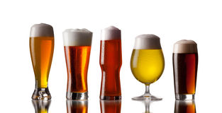 Several glasses of beer with cap of foam. Isolated in white Stock Photography