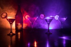 Several glasses of famous cocktail Martini, shot at a bar with dark toned foggy background and disco lights. Club drink concept. Selective focus royalty free stock photos