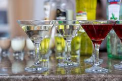 Several glasses of the famous Martini cocktail stand on a bar table.  Royalty Free Stock Photography