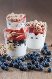 Several glasses full of yogurt, berrie and cereal and blueberries. On the wooden table royalty free stock photo