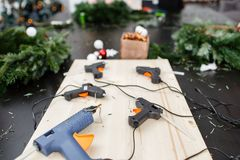 Several glue guns in the foreground on the Board. Manufacturer of Christmas wreath from branches of pine for holiday. Manufacturer of Christmas wreath from royalty free stock photo