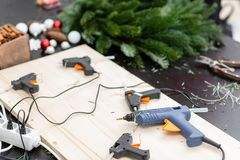 Several glue guns in the foreground on the Board. Manufacturer of Christmas wreath from branches of pine for holiday. Manufacturer of Christmas wreath from stock images