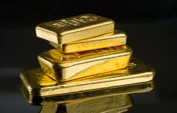 Several gold bars of different weight on a dark mirror surface.  stock images