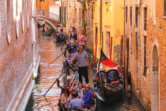 Several gondolas with tourists in a narrow channel. Venice, Ital Royalty Free Stock Image